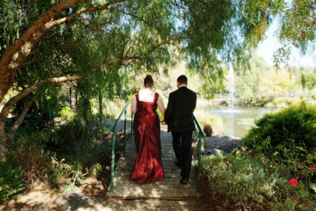 The Bride &amp; Groom Walk Away Through the Gardens at Fergussons Winery